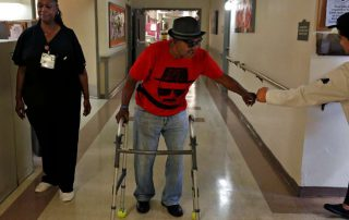 Nursing home resident walking down hall