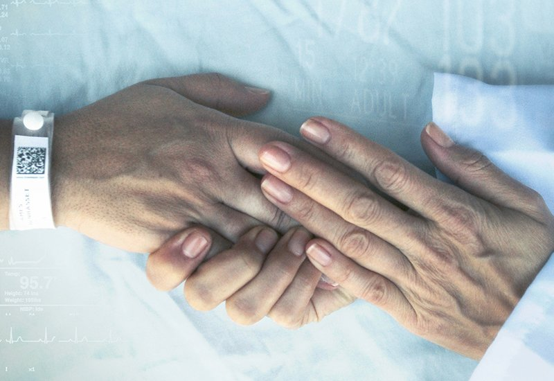 Closeup of a doctor clasping a patient's hands in theirs