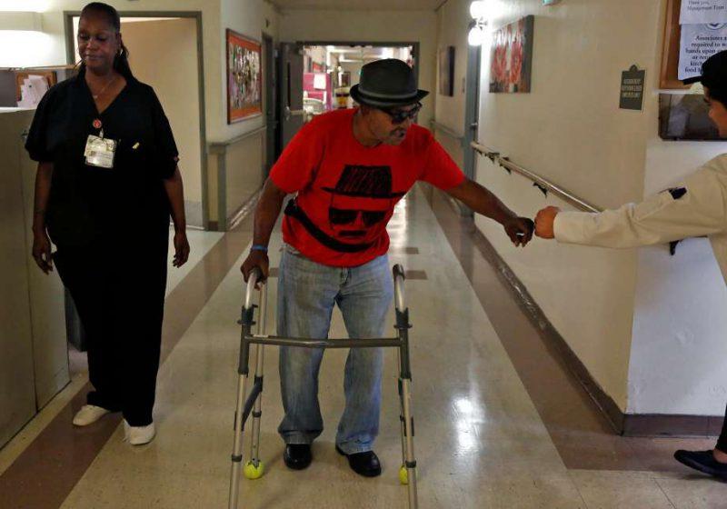 Nursing home resident walking down hall